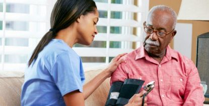 Senior Black Man Having Blood Pressure Taken by Nurse | Law Offices of David L Carrier