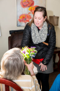 Hannah passes out Valentine's flowers to nursing home residents
