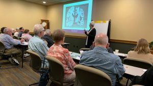 a presenter talks about dementia versus normal aging at a workshop at carrier law in grand rapids, mi